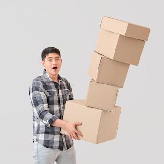 Homem asiático largando caixas móveis na luz