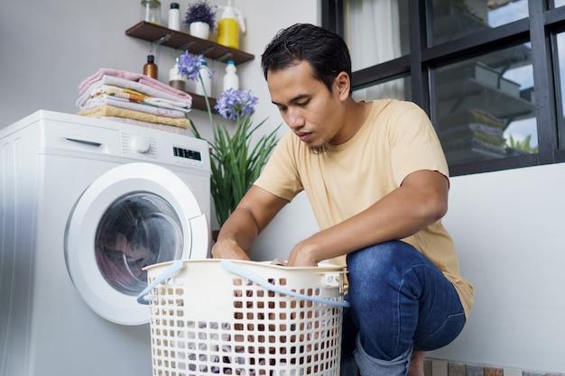 Homem asiático lavando roupa em casa carregando roupas na máquina de lavar