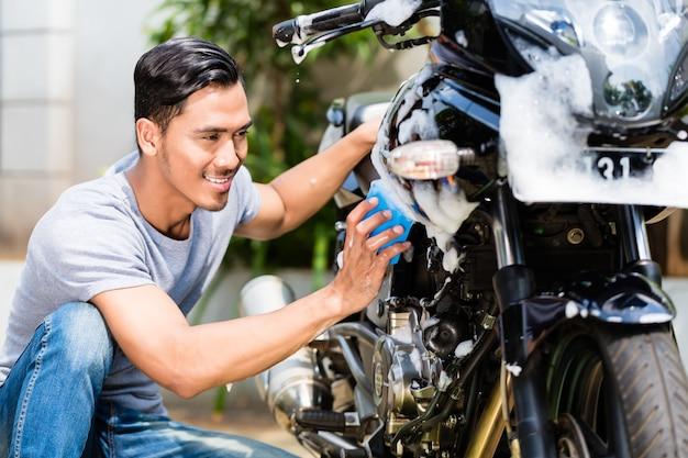 Homem asiático lavando sua motocicleta ou scooter com sabão e esponja
