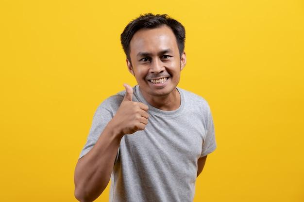 Homem asiático levanta o polegar para mostrar sucesso