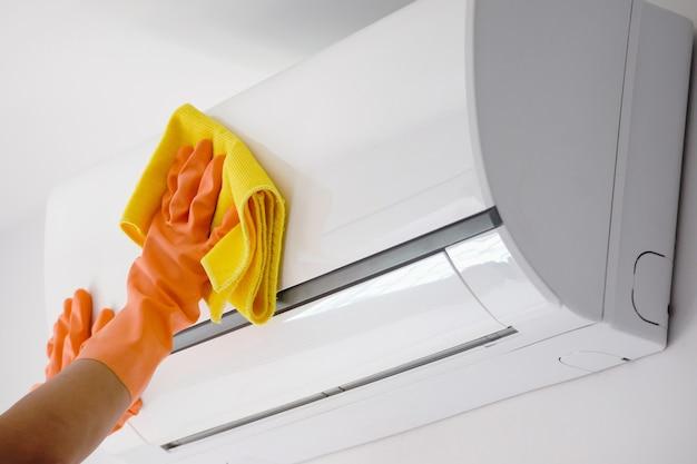 Homem asiático limpando ar condicionado com pano de microfibra