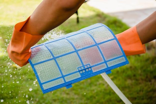 Homem asiático limpando filtro sujo de ar condicionado