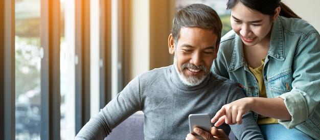 Homem asiático maduro da barba curto à moda atrativa do sorriso que usa o smartphone com jovem mulher.