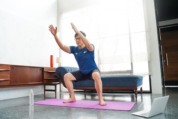 Homem asiático maduro fazendo exercícios em casa. treino em casa. distanciamento social.