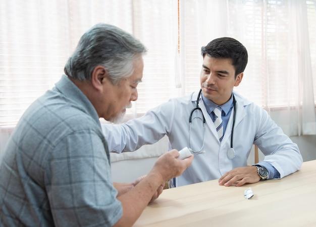 Homem asiático mais velho sênior perguntando jovem médico caucasiano sobre indicações e contra-indicações da nova medicina, cuidados de saúde e medicina conceito com espaço de cópia.