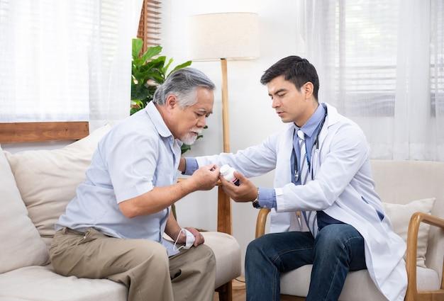 Homem asiático mais velho sênior perguntando jovem médico caucasiano sobre indicações e contra-indicações do novo medicamento.