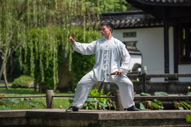 Homem asiático malhando com espada tai chi de manhã no parque, artes marciais chinesas