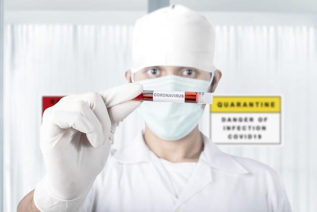 Homem asiático médico em máscara de gripe e luvas protetoras, segurando um tubo de ensaio com uma amostra de sangue de coronavírus