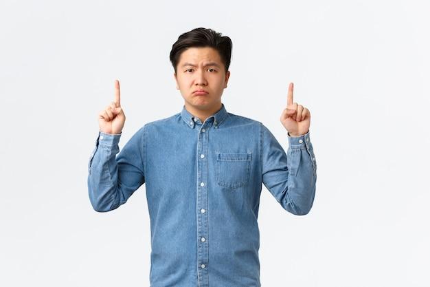 Homem asiático melancólico e chateado decepcionado informar sobre más notícias tristes, apontando o dedo para cima e olhando para a câmera descontente, reclamando, sentindo-se inquieto, fundo branco em pé.