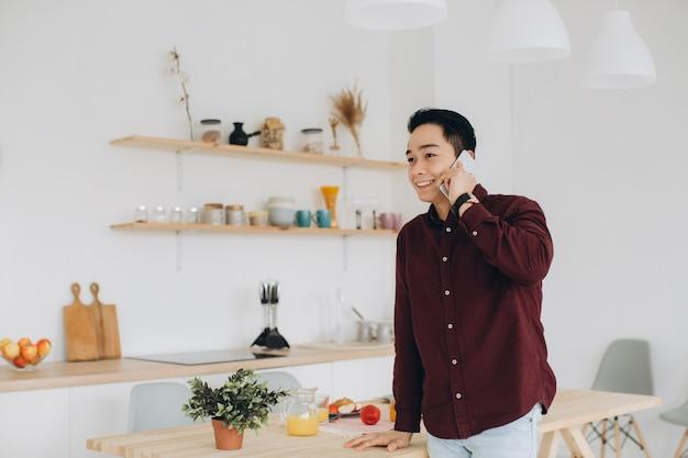 Homem asiático moderno falando ao telefone na cozinha no café da manhã.