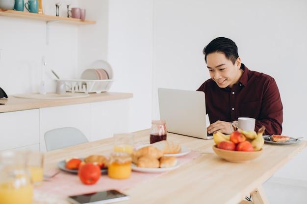 Homem asiático moderno trabalhando no laptop na cozinha no café da manhã.