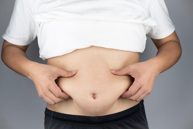 Homem asiático mostrando a barriga e levantando as mãos, pegando o gordo na pança