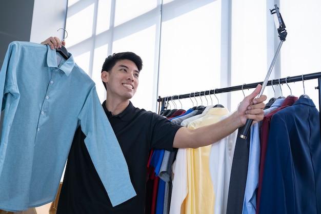 Homem asiático mostrando a camisa em um rosto. ligue para o mercado online