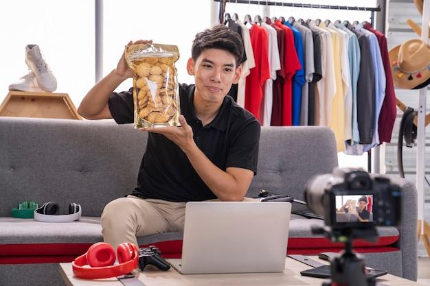 Homem asiático mostrando biscoitos em uma chamada facial em seu laptop enquanto está sentado em um sofá em uma loja de roupas.