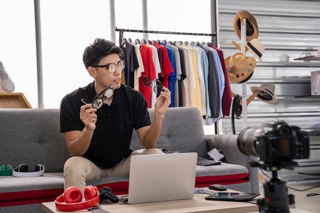 Homem asiático mostrando óculos em um facecall em seu laptop enquanto está sentado em um sofá em uma loja de roupas.