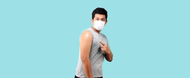 Homem asiático mostrando seu braço vacinado em um fundo azul em estúdio com espaço de cópia