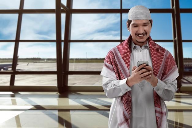 Homem asiático, muçulmano, ligado, aeroporto