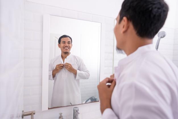 Homem asiático muçulmano olhando no espelho e se vestindo antes de ir para a mesquita