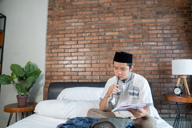 Homem asiático muçulmano segurando a lista de verificação de papel para bagagem