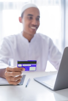Homem asiático muçulmano usando cartão de crédito para transação de pagamento na loja online
