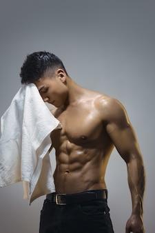 Homem asiático muscular cansado dentro de casa