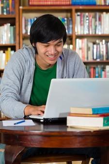 Homem asiático na biblioteca com laptop
