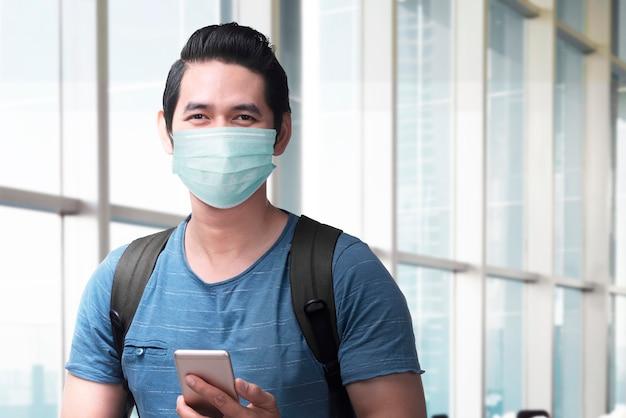 Homem asiático na máscara facial com uma mochila segurando o smartphone no terminal do aeroporto. viajando no novo normal