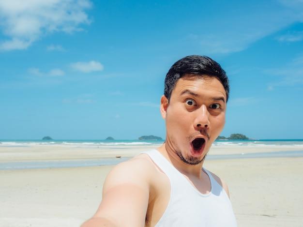 Homem asiático na viagem ensolarada da praia do verão.