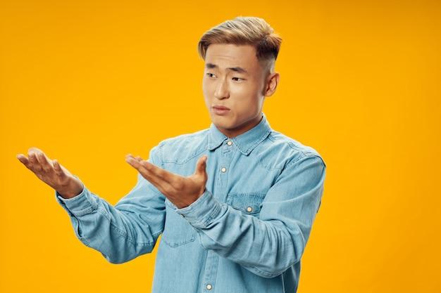 Homem asiático no espaço de cores brilhantes, posando de modelo, coronavírus