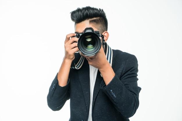 Homem asiático novo com a câmera isolada no fundo branco. conceito de fotógrafo