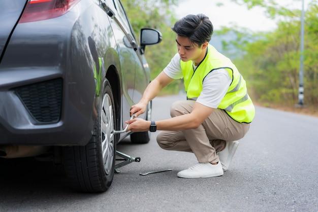 Homem asiático novo com o colete verde da segurança que muda o pneu furado em seu carro que afrouxa as porcas com uma chave de roda antes de levantar o veículo na estrada secundária em tailândia.