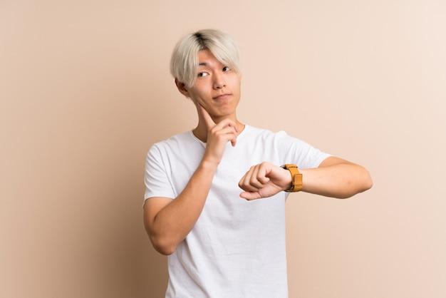 Homem asiático novo com relógio de pulso e pensando uma ideia