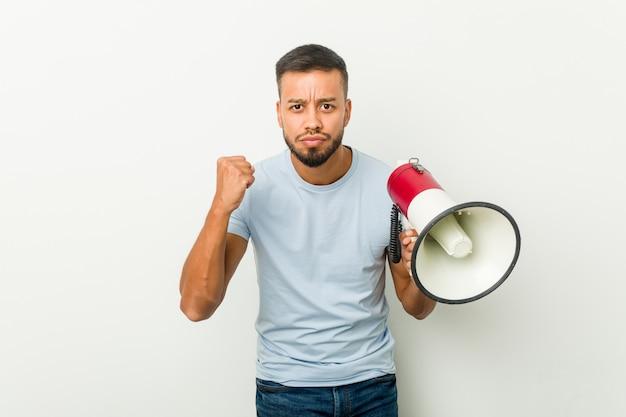 Homem asiático novo da raça misturada que guarda um megafone que mostra o punho à câmera, expressão facial agressiva.