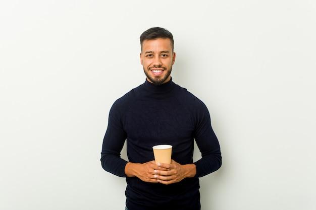 Homem asiático novo da raça misturada que mantém um café afastado feliz, sorridente e alegre.