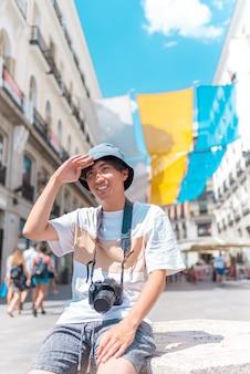 Homem asiático novo do turista que senta-se ao ar livre com uma câmera.