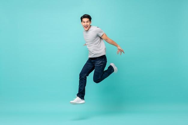 Homem asiático novo feliz energético na roupa ocasional que salta