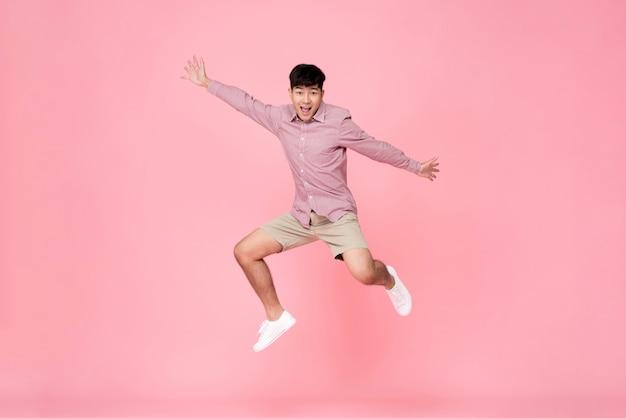 Homem asiático novo feliz energético que salta