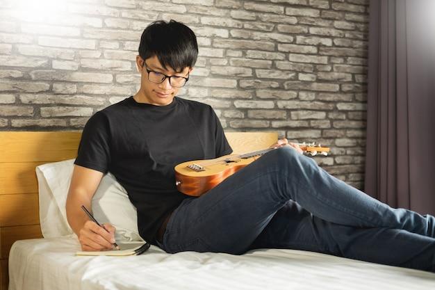 Homem asiático novo feliz que joga a uquelele que senta-se na cama no quarto.