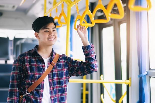 Homem asiático novo que guarda o punho do ônibus público.