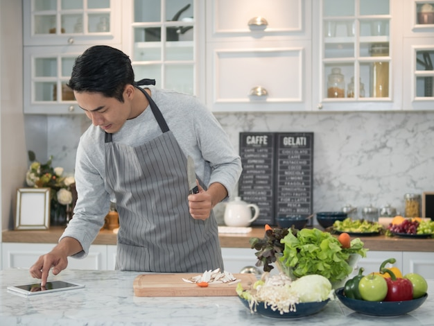 Homem asiático novo que olha a receita na tabuleta digital e que cozinha o alimento saudável na cozinha em casa.