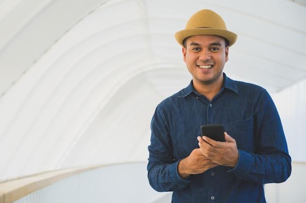 Homem asiático novo que usa o smartphone.