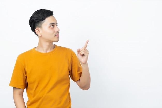Homem asiático novo saudável feliz que sorri com seu dedo que aponta até o copyspace no fundo branco.