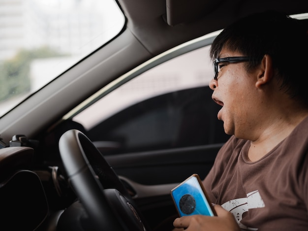 Homem asiático obeso e sonolento bocejando e segurando o smartphone na mão enquanto dirige o carro, perigo e distração ao dirigir na estrada, viciado em smartphone