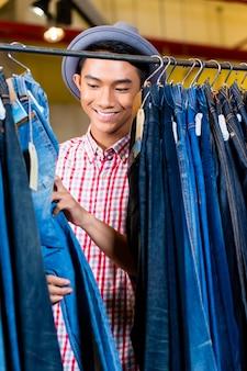 Homem asiático olhando jeans pendurados em um cabideiro em loja de moda