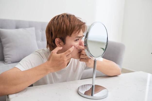Homem asiático olhando no espelho e estourando uma espinha
