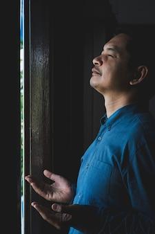 Homem asiático orando por graças a deus no quarto escuro.
