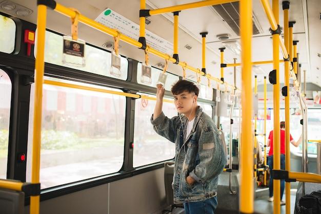 Homem asiático, pegando transporte público, dentro do ônibus.