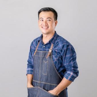 Homem asiático posando com uniforme de barista