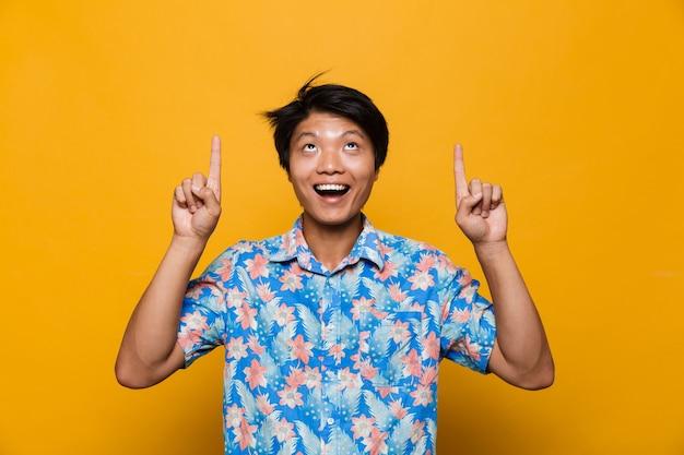 Homem asiático posando isolado sobre o espaço amarelo apontando.