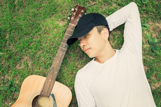 Homem asiático que dorme na grama com a guitarra sob o pinheiro.